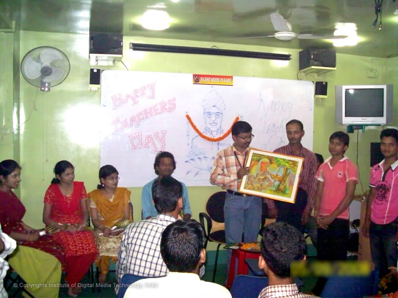 Students presenting a handmade painting with lots of love to their honorable teachers, on the occasion of Teacher's Day celebration at IDMT.
